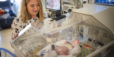 Dr. Kristin Hoffman demonstrating webcam technology in the NICU. (c) UC Regents. All rights reserved
