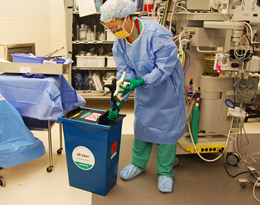 nurse in the operating room, places instruments used in endoscopic surgeries into a bin for reprocessing