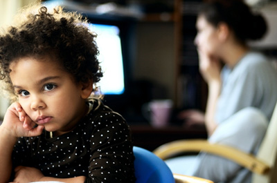 Bored child staying indoors with her mother © iStockphoto