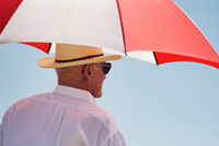Man walking in sun with umbrella © iStockphoto