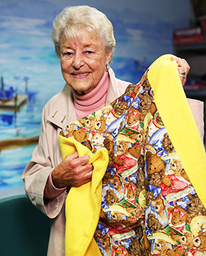 Sally Coyle displays a quilt she made for UC Davis Children's Hospital © UC Regents