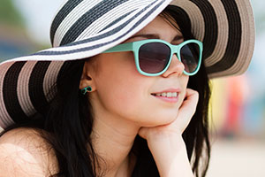 Photo of teen wearing hat and sunglasses at the beach. © iStockphoto