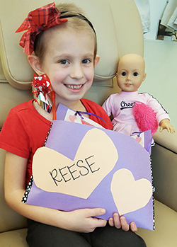 Photograph of Reese and her doll during treatment at UC Davis Children's Hospital © UC Regents