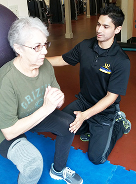 Eddie Salazar, Sacramento cancer survivor and Triumph Fitness physical therapy instructor, works with a participant on new exercise techniques.