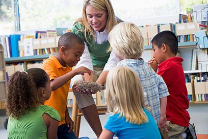 Kindergarten teacher with children looking at a bird nest