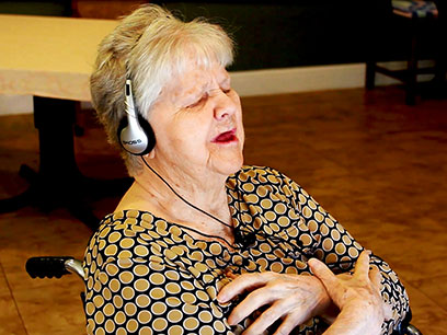 Betty Irene Moore School of Nursing at UC Davis study participant Gertrude Lasley wears iPod headphones to listen to her favorite tunes