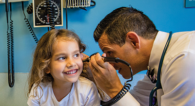 Doctor looking into a pediatric patients ear