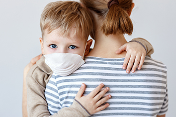 child wearing a mask holding onto his mother