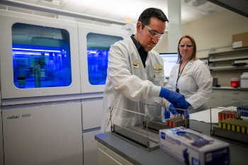 Lab scientists Marcelo Prado and Katie Zegarski prepare the cutting-edge lab robot to run hundreds of combined COVID-19/flu tests daily.