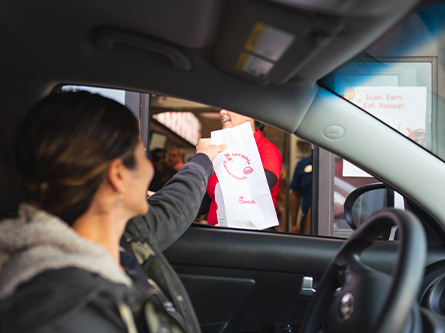 Bag of food being obtained at drive thru window