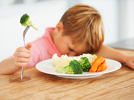 Blond kid sulks next to plate of veggies