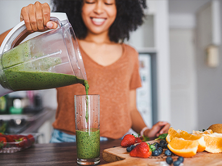 Woman pouring healthy green smoothie
