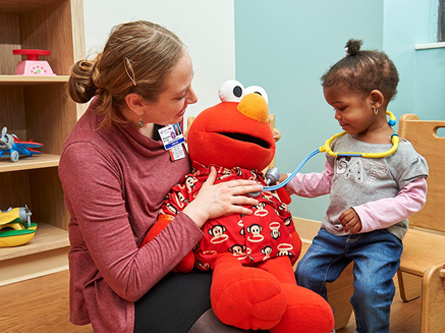 Doctor holds Elmo doll and child checks Elmo's heart with stethoscope.