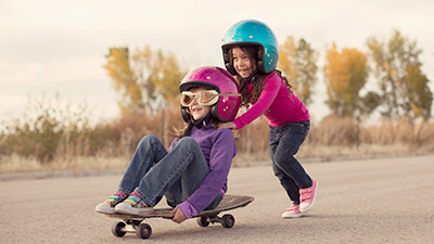 stock image of two girls with helmets on skateboard