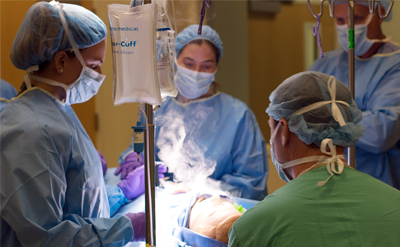 Clinicians practice ENT surgical procedures on a mannequin. (C) UC Davis Regents.