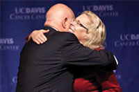 UC Davis Health System Vice Chancellor Claire Pomeroy congratulates Ralph de Vere White, cancer center director