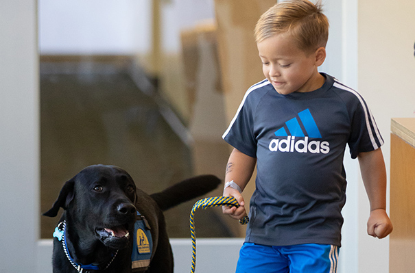 Fritz Stark and Huggie the UC Davis therapy dog trained to support kids with cancer.