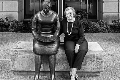 Ruth Rippon sitting with her bronze statue Waiting