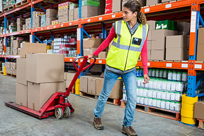Woman pulling hand truck in a warehouse