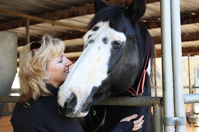Woman face-to-face interacting with horse in a barn