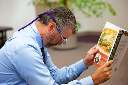 UC Davis Eye Center staff member shown using mirrored-prism glasses to read a book as a patient would after retinal surgery using gas.