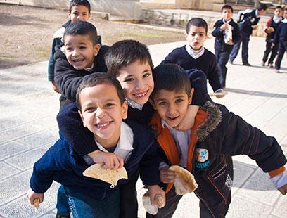 Boys in school yard at recess eating snacks