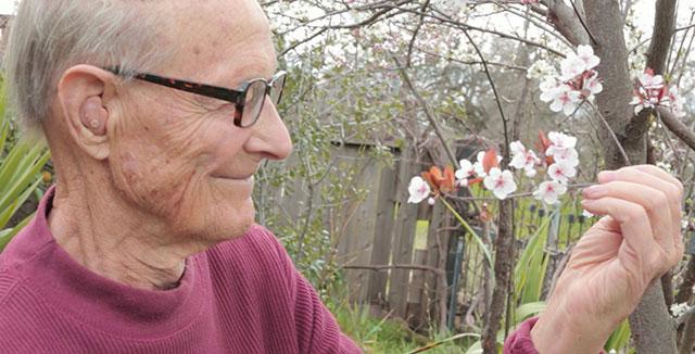Ernest Tschannen with a flower in his garden.  © UC Regents