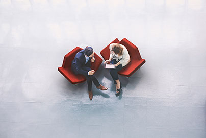 Two people in chairs having a business discussion © iStock