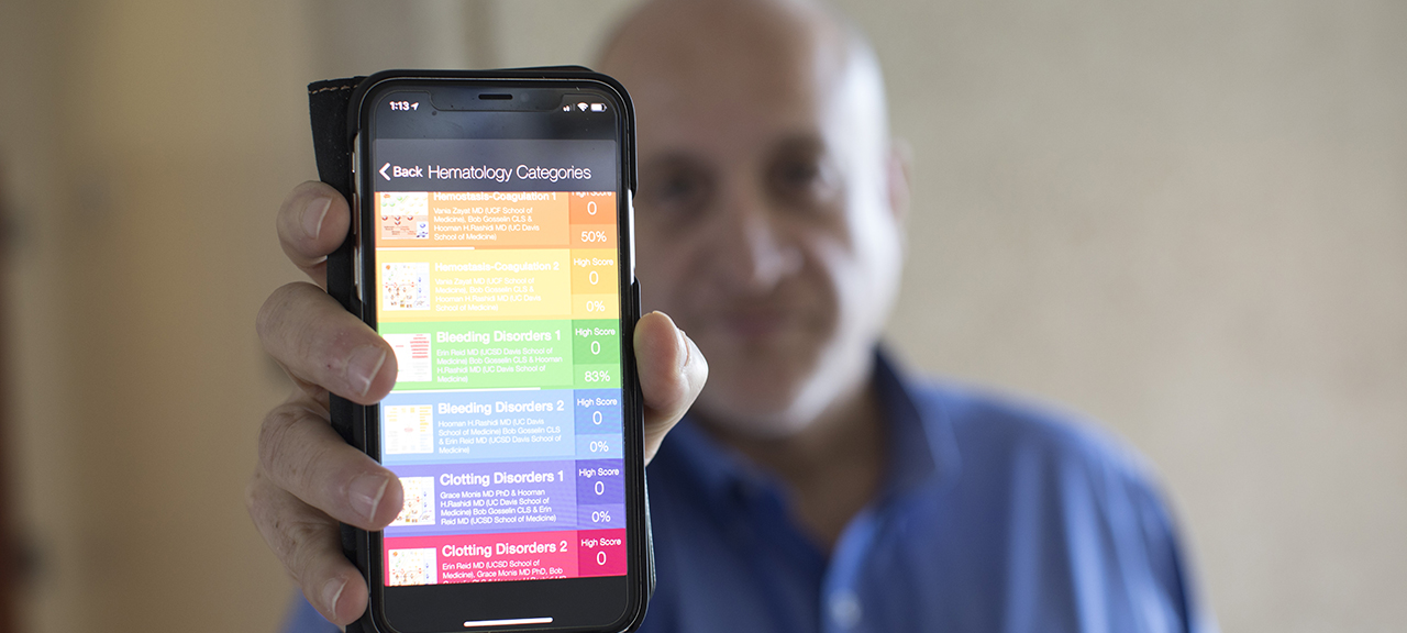 Dr. Rashidi holding his smartphone with his app on the screen