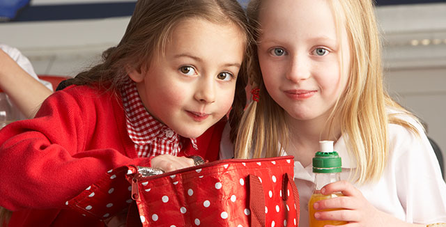 Two girls sharing a lunch and juice