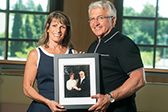 Photograph of Lynn and Keith Volkerts with a framed photo of Lynn's late parents George and Lena Valente.